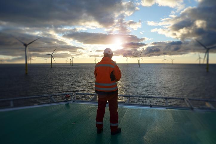 An offshore wind turbine technician aboard sea vessel looks out on offshore windfarm