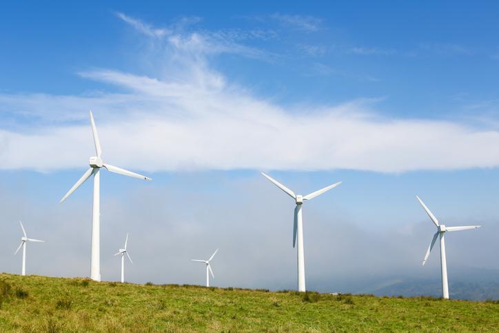 An onshore wind farm shows six wind turbines