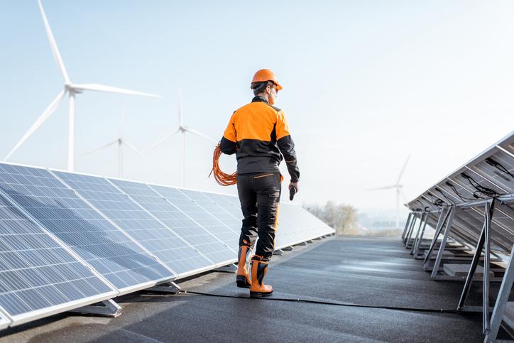 A wind turbine technician walks beside row of solar panels with wind turbines in distance