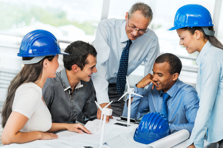 A group of wind turbine tech trainees view plans with profofessional