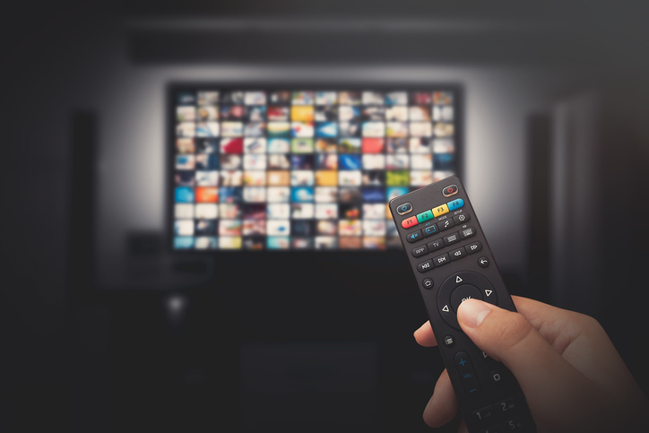 A viewer holding remote selects streaming channel from flatscreen TV
