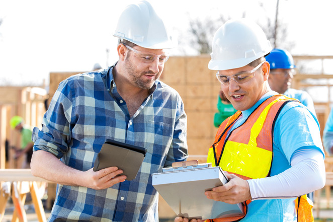A construction project manager confers with a construction worker