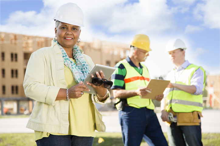 A construction manager with tablet stands in front of two conferring construction workers
