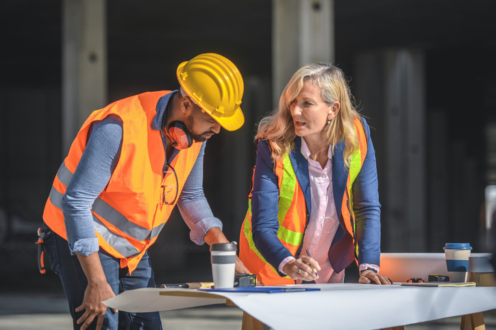 A construction manager discusses project plans with construction worker