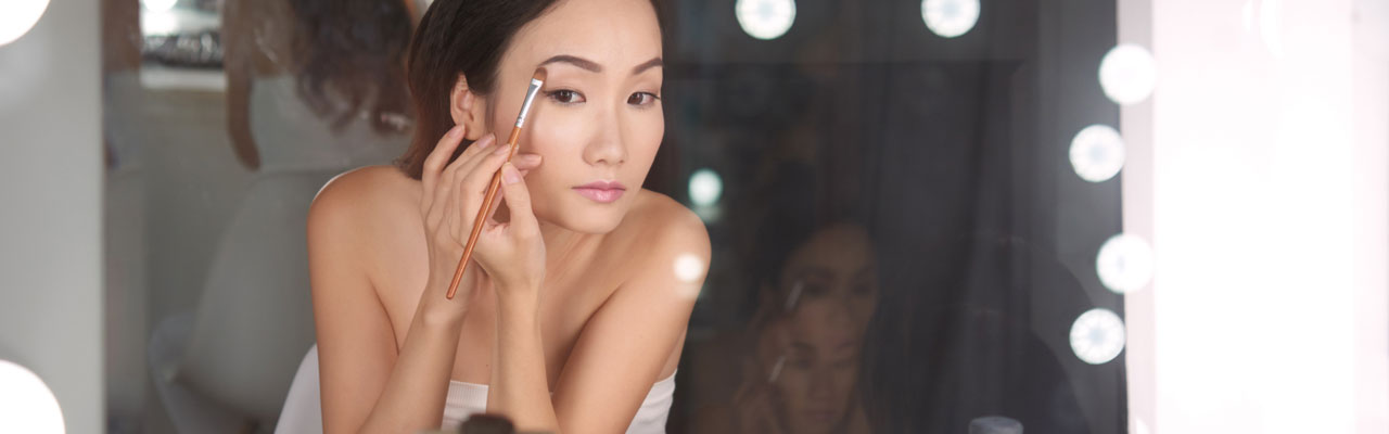 woman looking into a vanity mirror putting on eye shadow