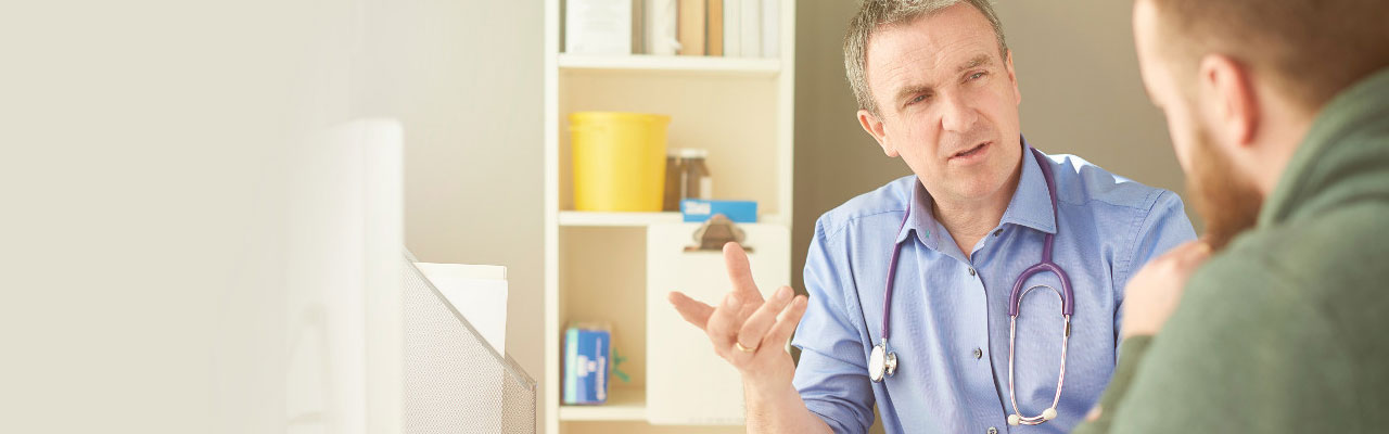 healthcare professional with stethoscope around his neck talking to patient in office