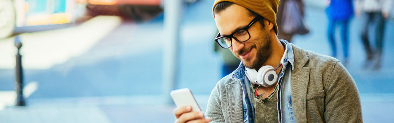 male hipster with dark rimmed glasses, wearing a beanie and white headphones around his neck looking at his smartphone