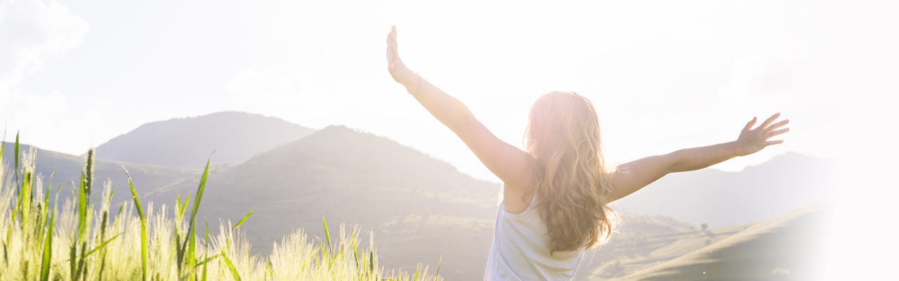 woman outdoors stretching her arms wide as the suns shines with mountains in the background