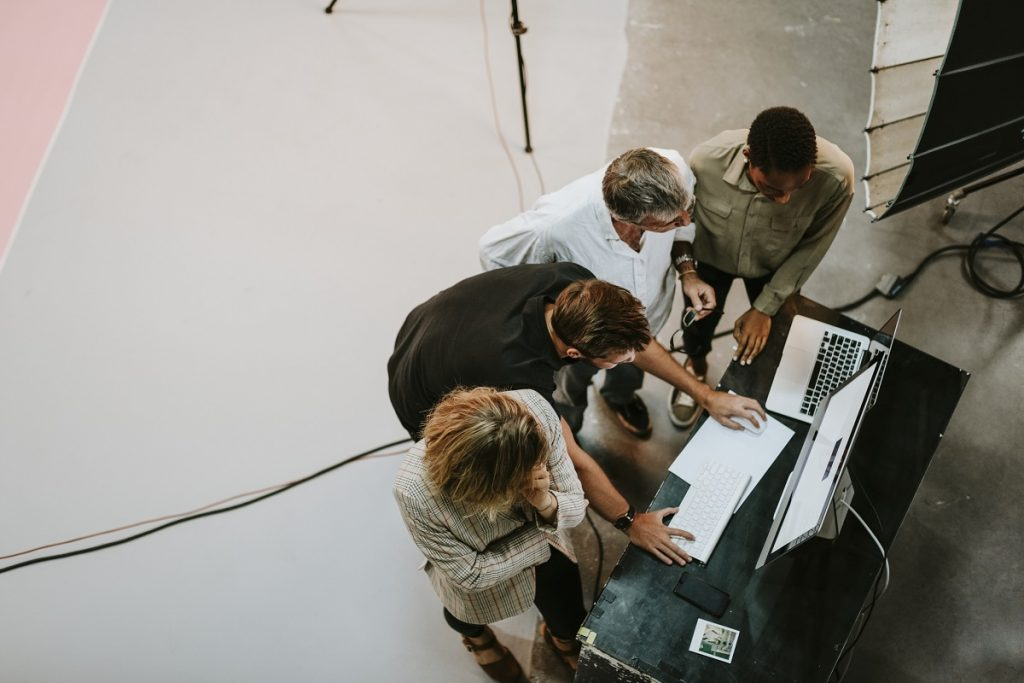 birds-eye view of four professionals standing over a laptop computer trying to figure out a solution to a problem