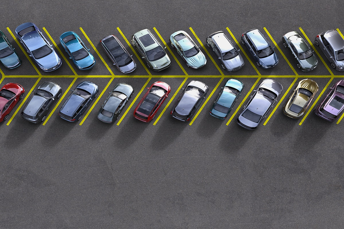 aerial view of a parking lot lane, each spot filled with a different car