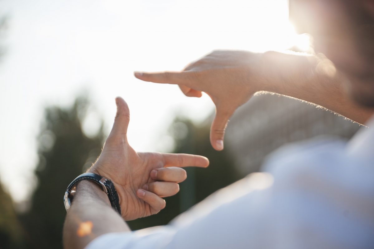 person holding up both hands in inverted L shapes in front of them framing something off in the distance with their index fingers and thumbs