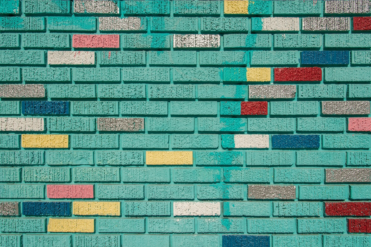 brick wall painted green with intermittent bricks colored in yellow, blue, red, orange, and white