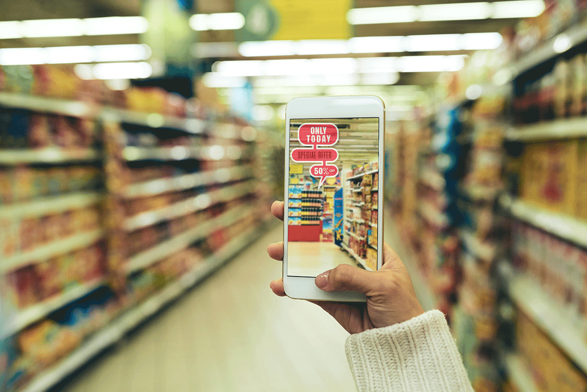 hand holding up a smartphone with a picture of the grocery aisle on it with signage generated by augmented reality technology
