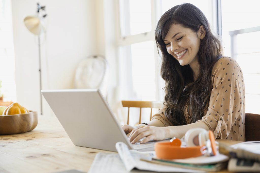 woman sitting at her dining room table, smiling while she views something on her laptop