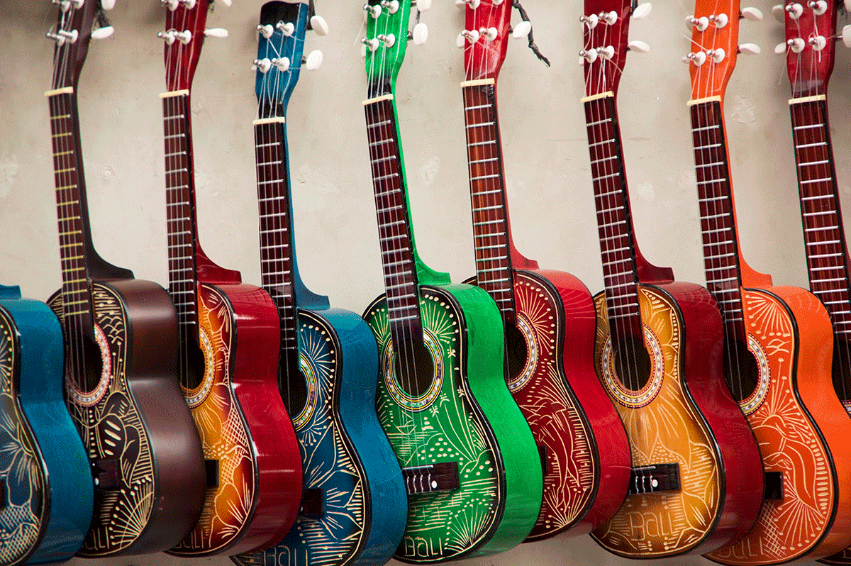 nine guitars in a range of different colors leaning against a wall showcasing hyper-personalization