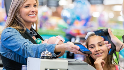 mother and daughter at the grocery store check out counter paying for their groceries