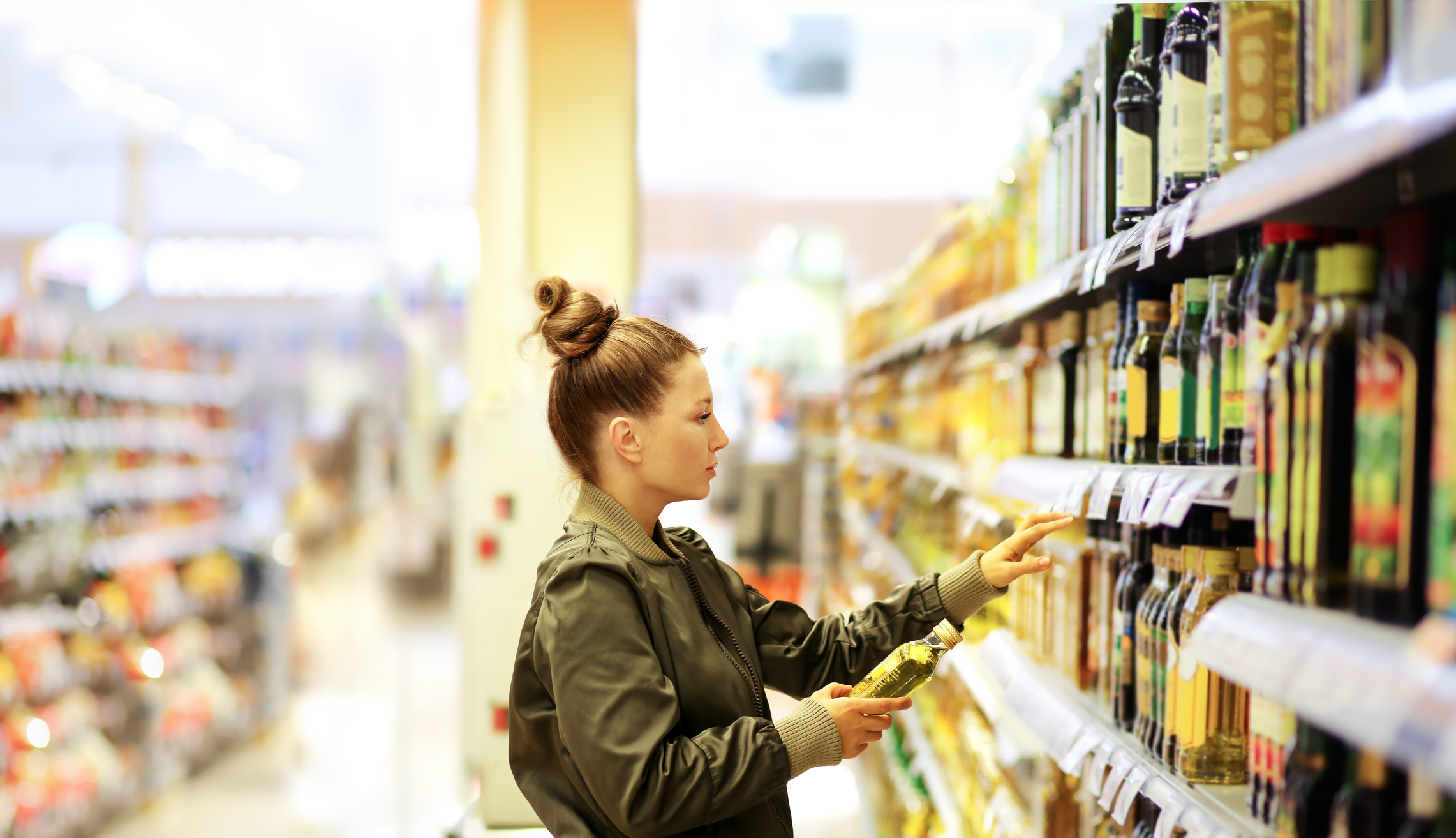 woman in dark green jacket looking at different product choices in the aisle of a grocery store