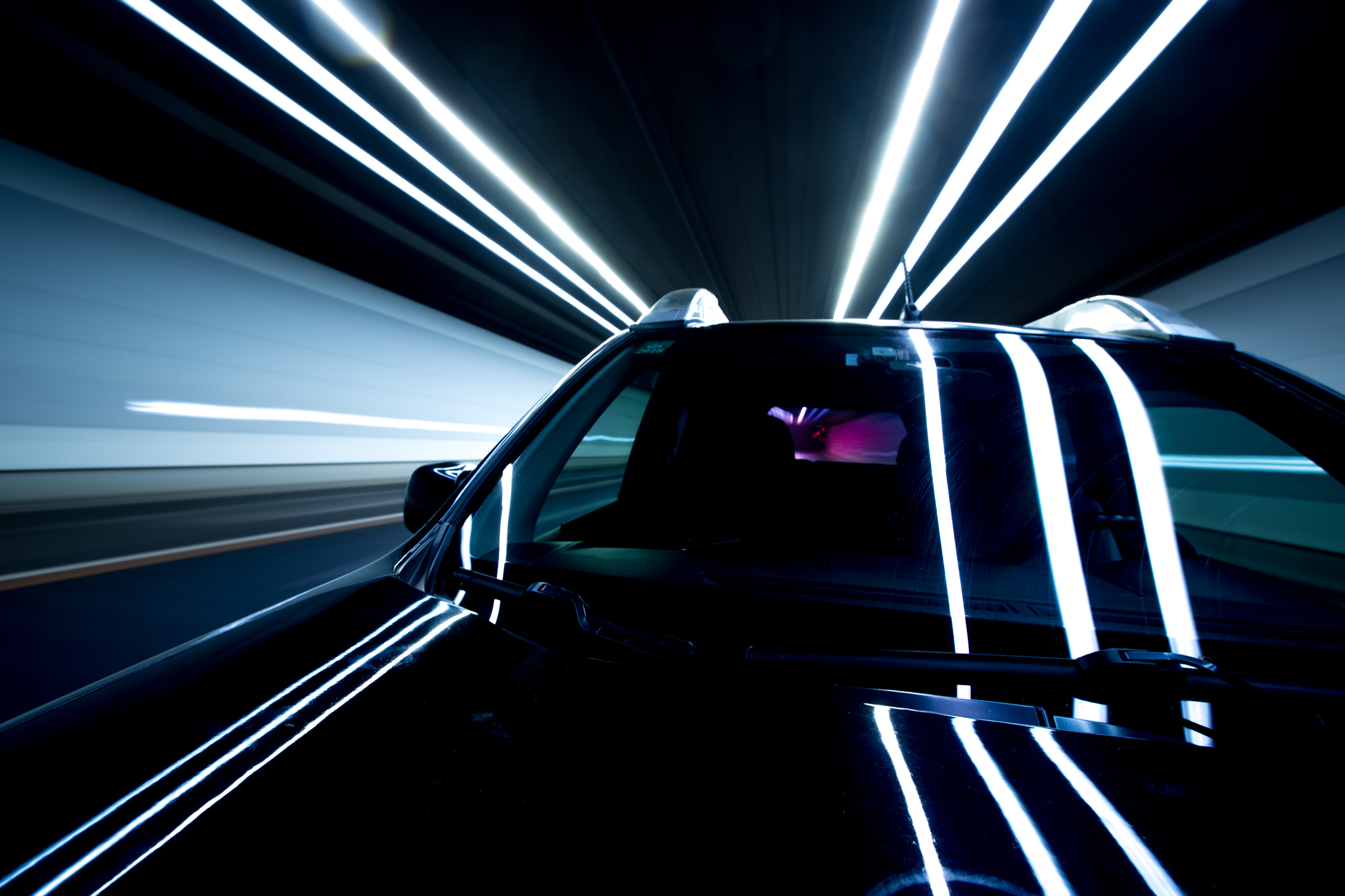 close-up of black car in motion inside lit tunnel