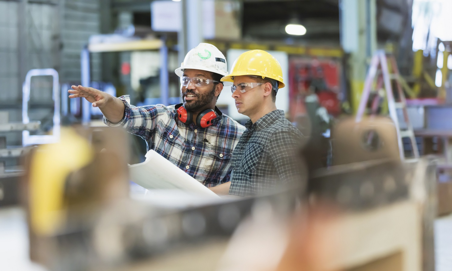 two men in a warehouse wearing hard hats, protective glasses and wearing their hearing protection over their shoulders discussing the blue print plans they're holding