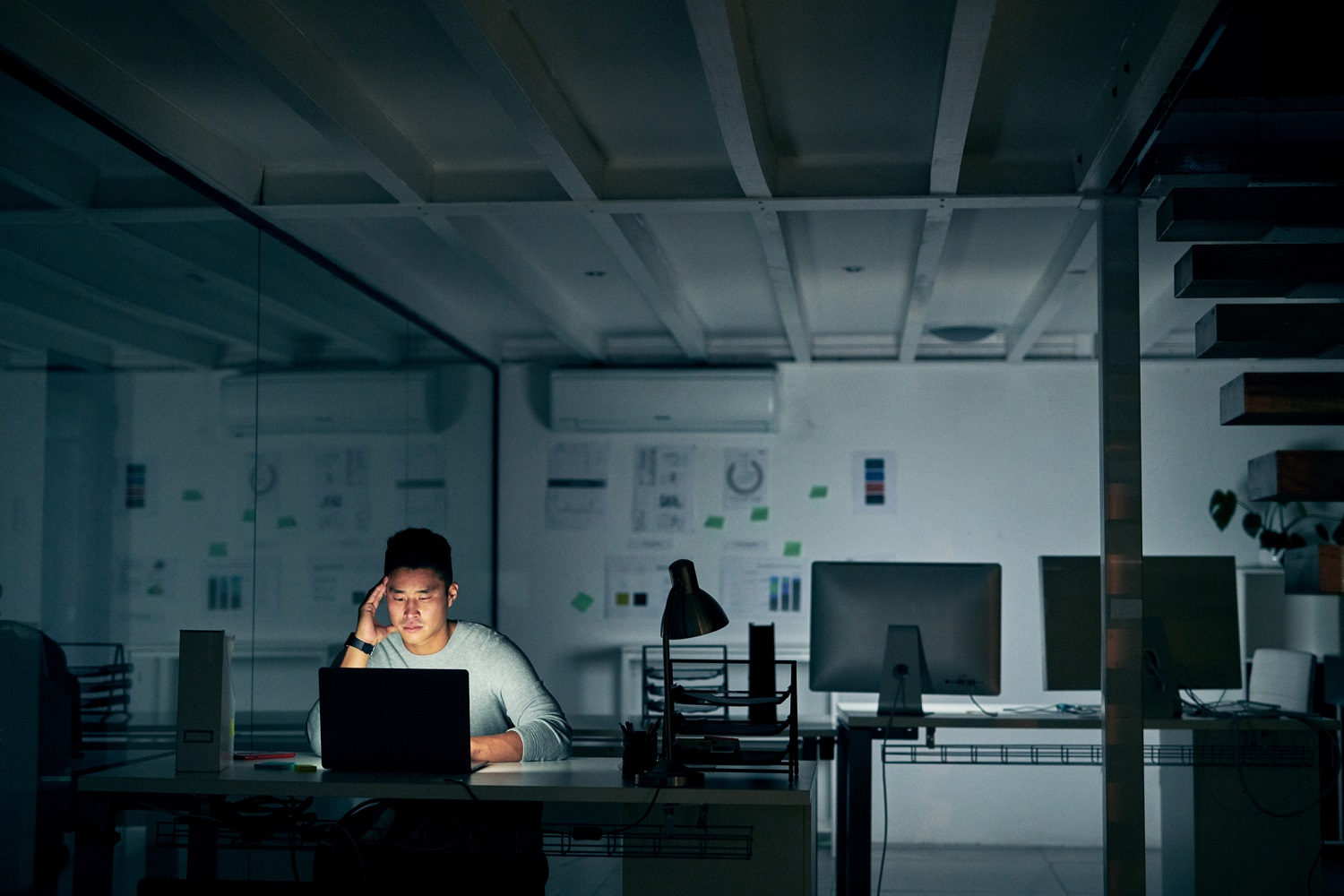 man sitting at his desk in a dark office with light only emanating from his monitor appears to be frustrated having to work late into the evening