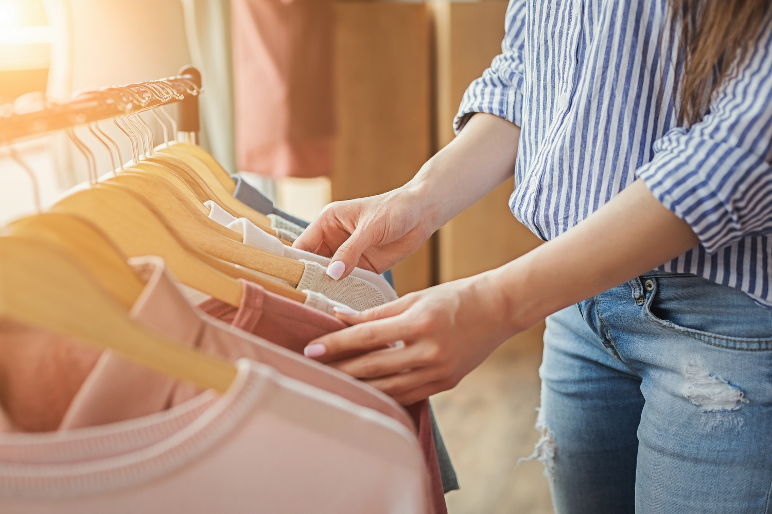 female shopper looking through tops hanging on a clothing rack