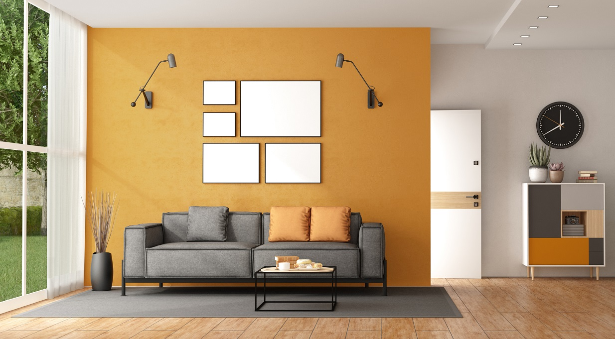 modern living with gray couch in front of yellow wall