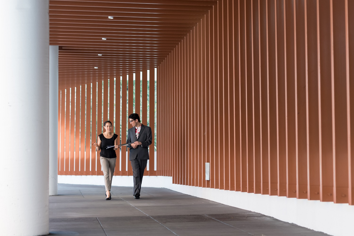 two people in business attire walking down an outdoor corridor having casual conversation