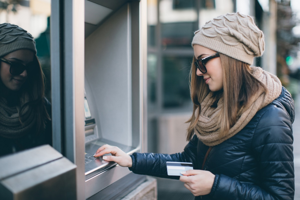 female millennial in winter coat and hat at an atm holding a debit card