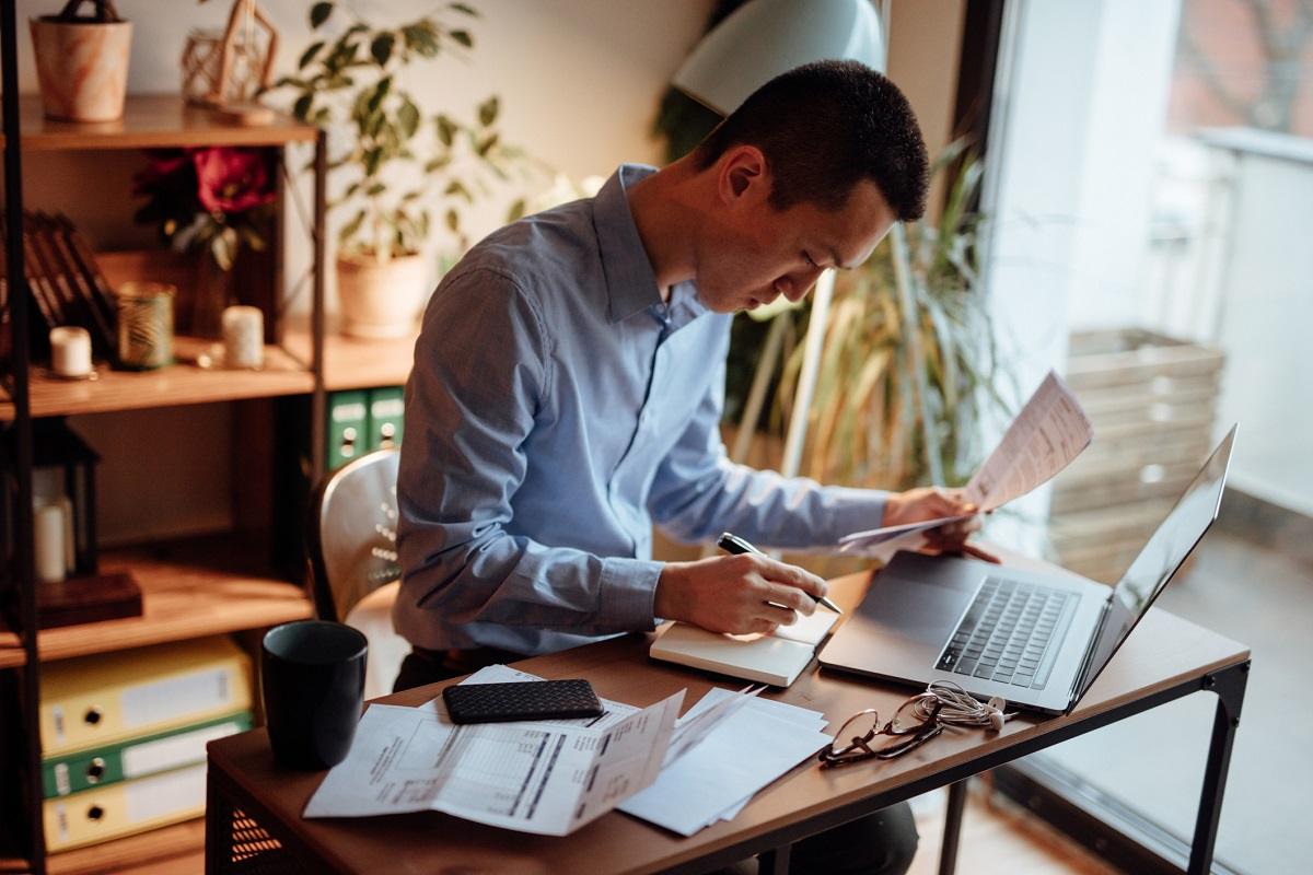 man in blue button down shirt sitting in home office paying bills on laptop