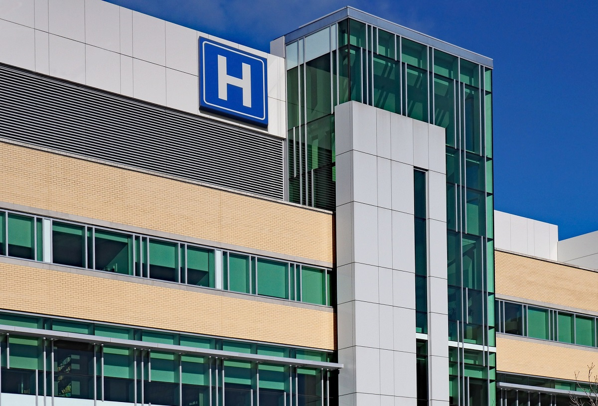exterior view of a hospital with blue H hospital sign