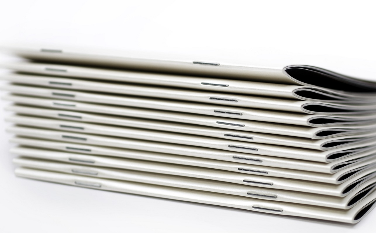 stack of white magazines with saddle stitch binding