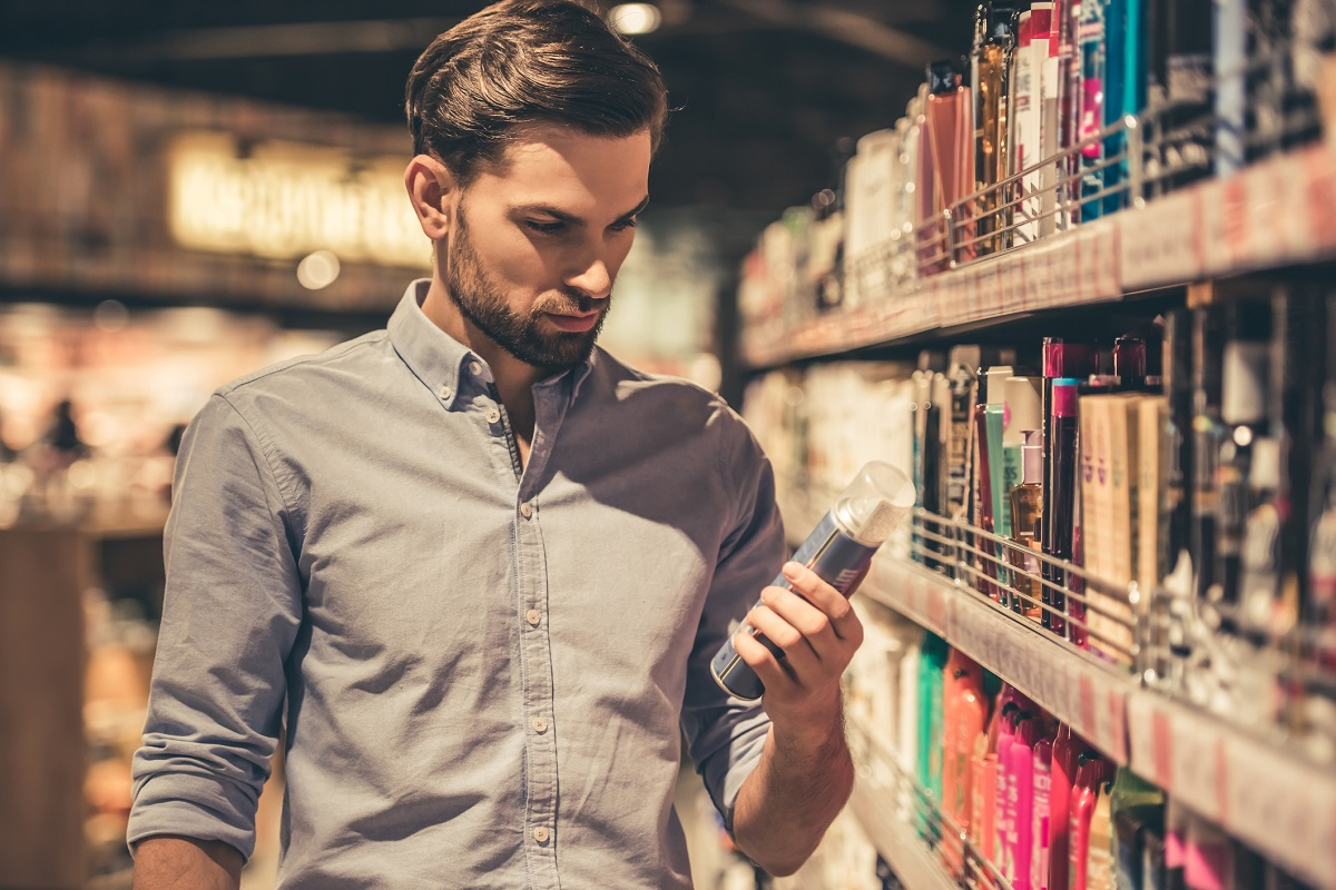 bearded man in button-down shirt holding a product in the grooming aisle