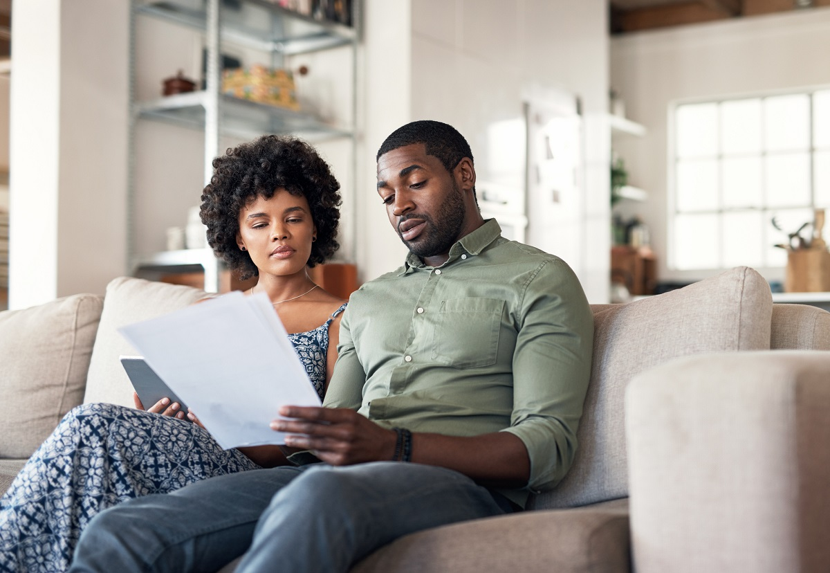 couple sitting together on couch looking at paperwork