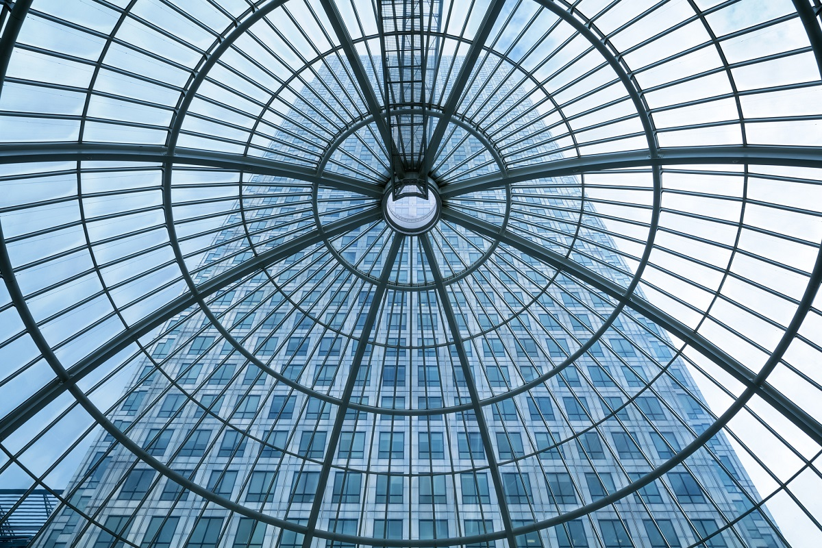 upward view of glass ceiling with a tall building in the background