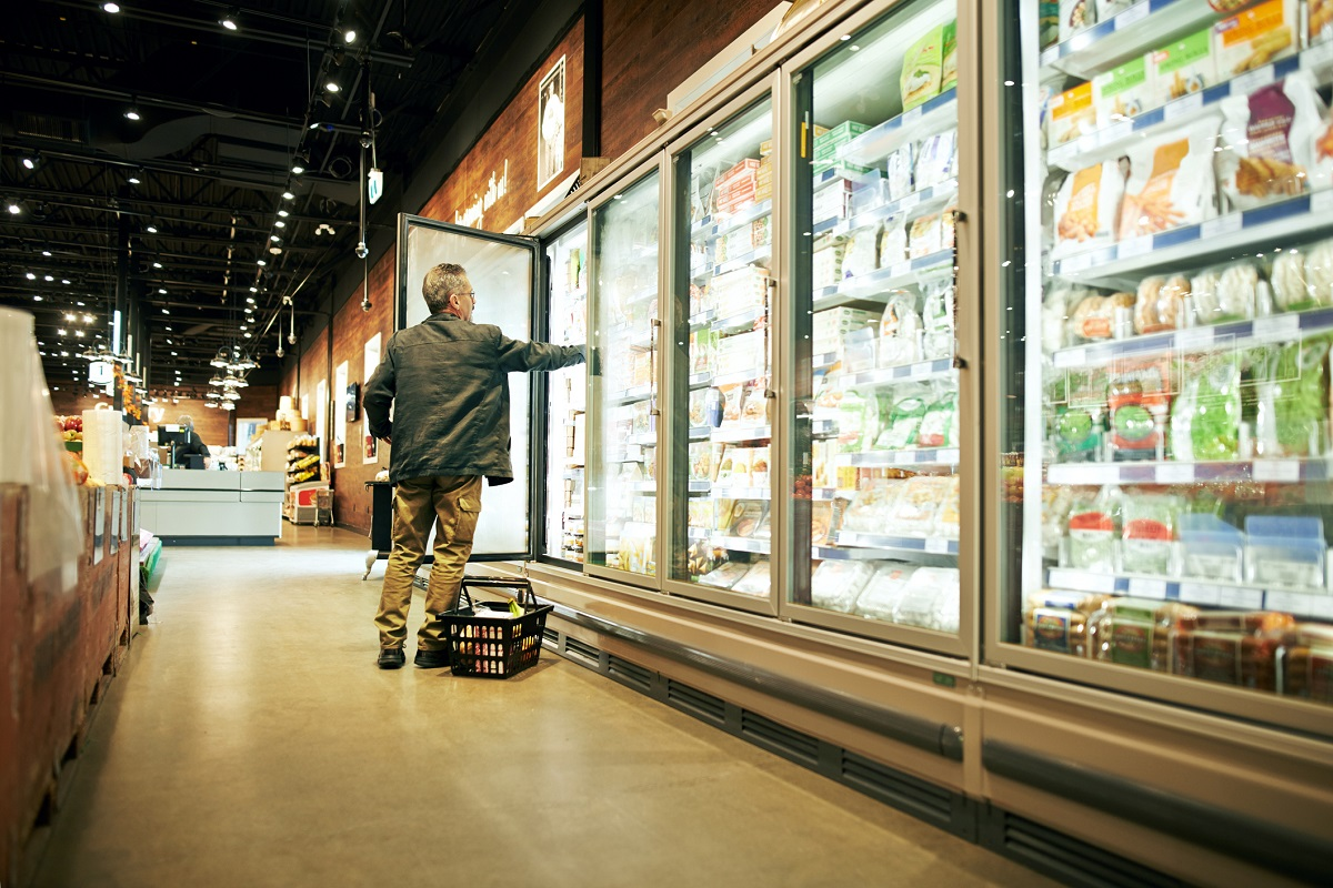 man at grocery store holding door open in the frozen aisle and reaching in