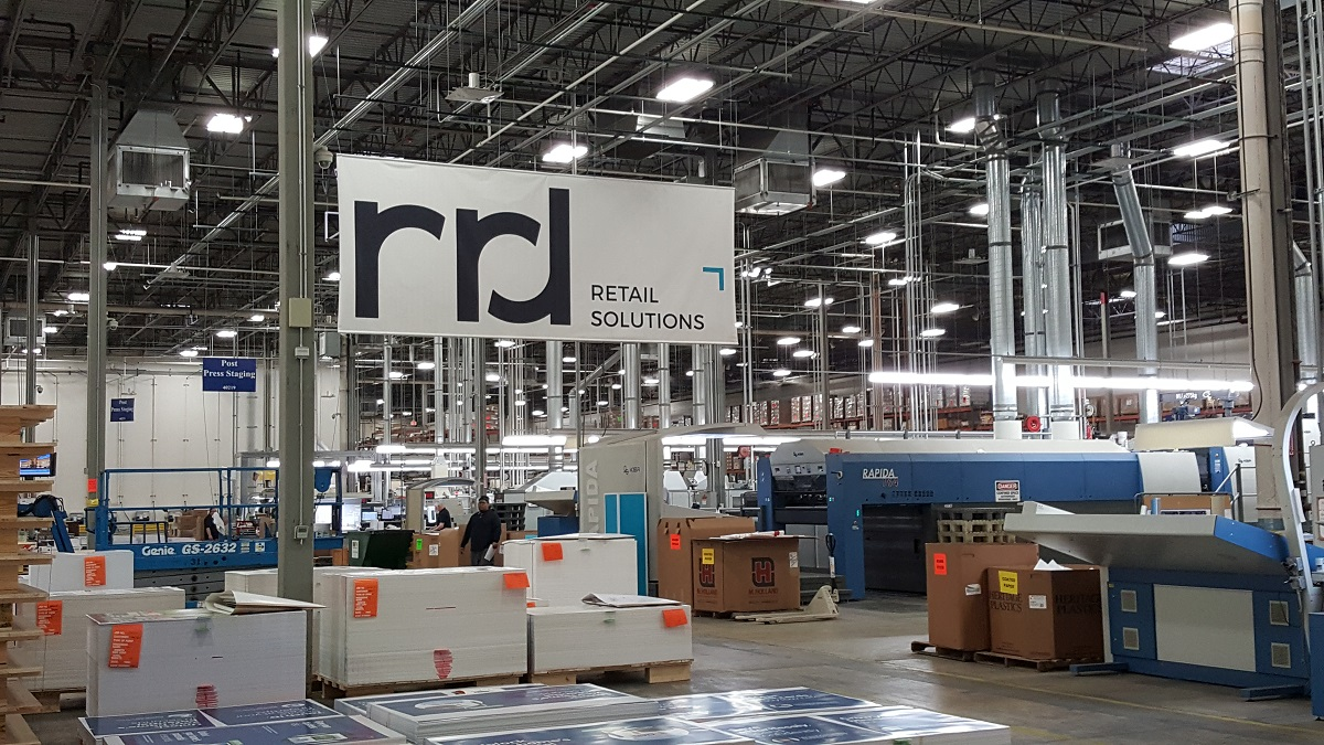 a large, open warehouse with large machines, boxes on pallets and a large canvas banner that says rrd retail solutions