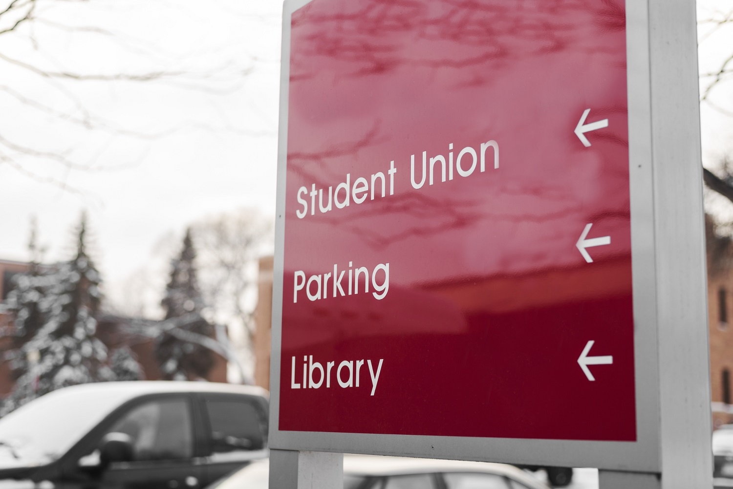 red sign at university that reads student union, parking, library