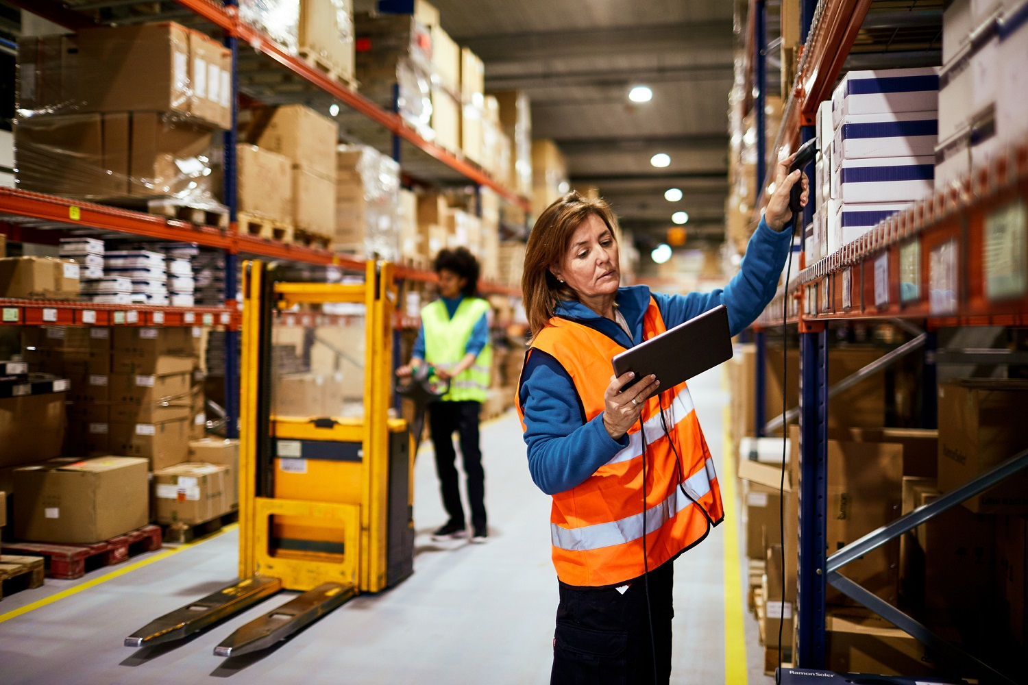 one female warehouse worker in bright yellow vest operating forklift as another female warehouse worker in a bright orange vest scans a label in a box