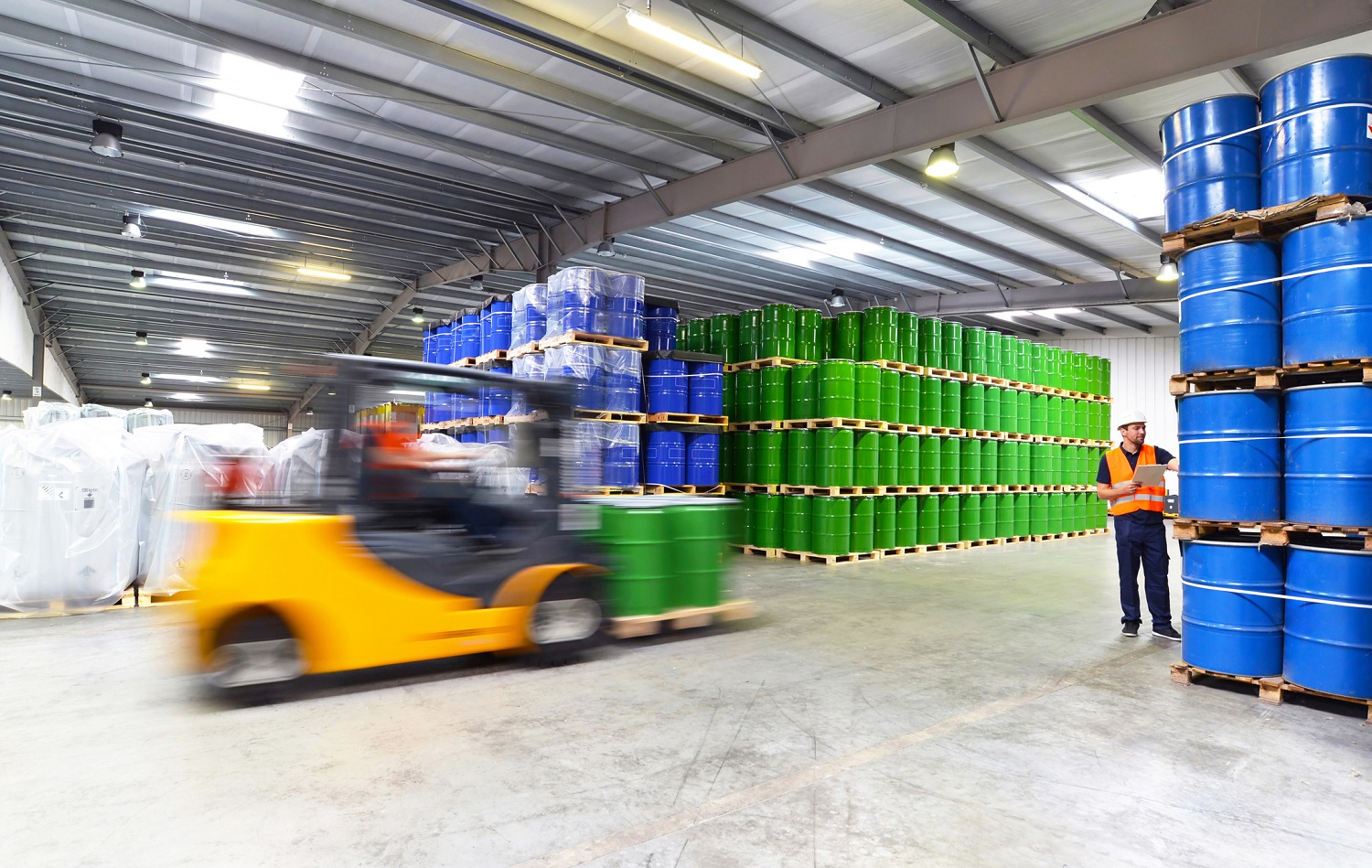 forklift and two workers in orange vests in a warehouse filled with blue and green drums stacked to the ceiling