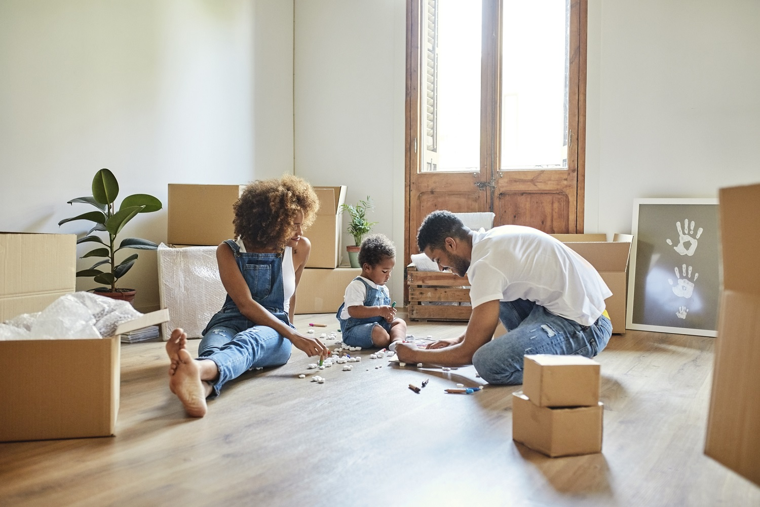 mom and dad with young child playing with small toys in the center of a room filled with moving boxes
