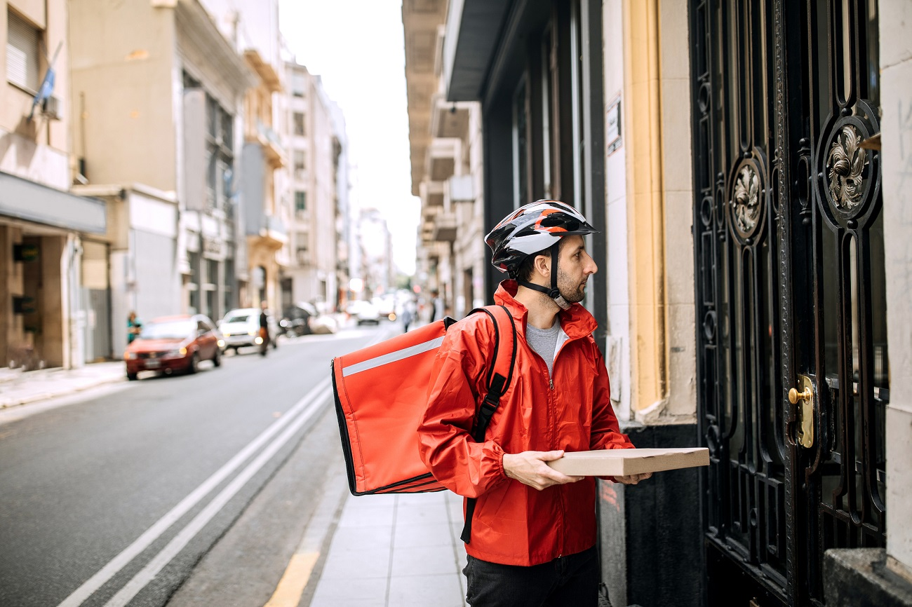pizza delivery man in red jacket and bike helmet delivering one pizza