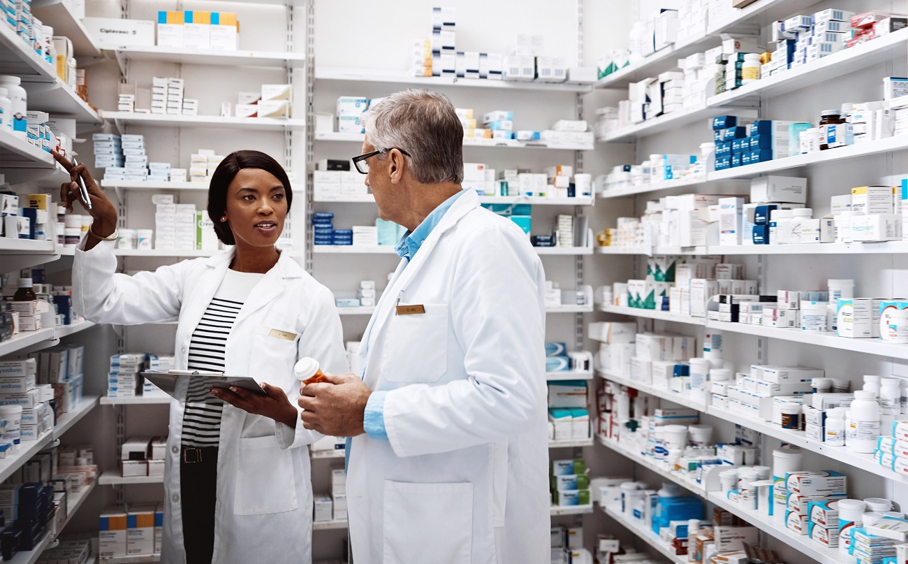 one female pharmacist and one male pharmacist in white coats talking to each other in pharmacy stock room