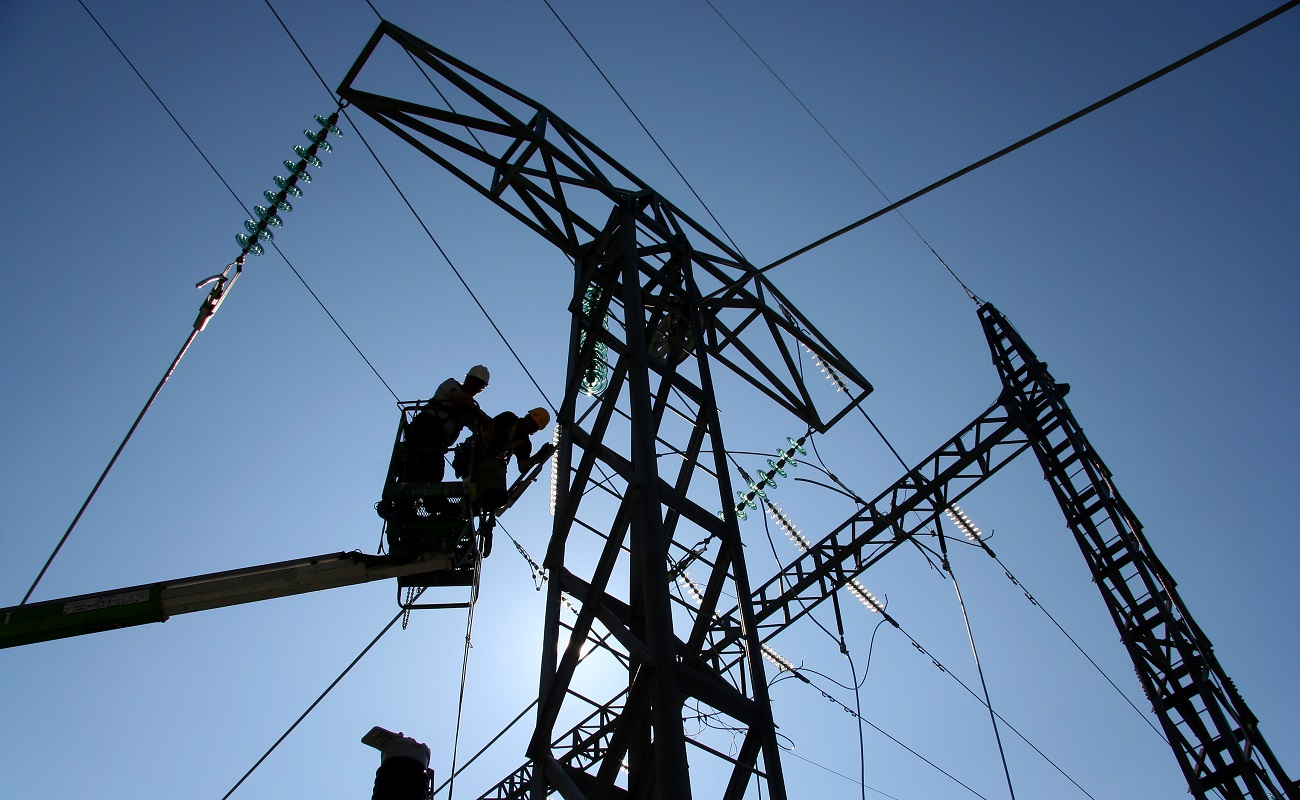 two utility workers on a lift working on power lines with blue sky behind them