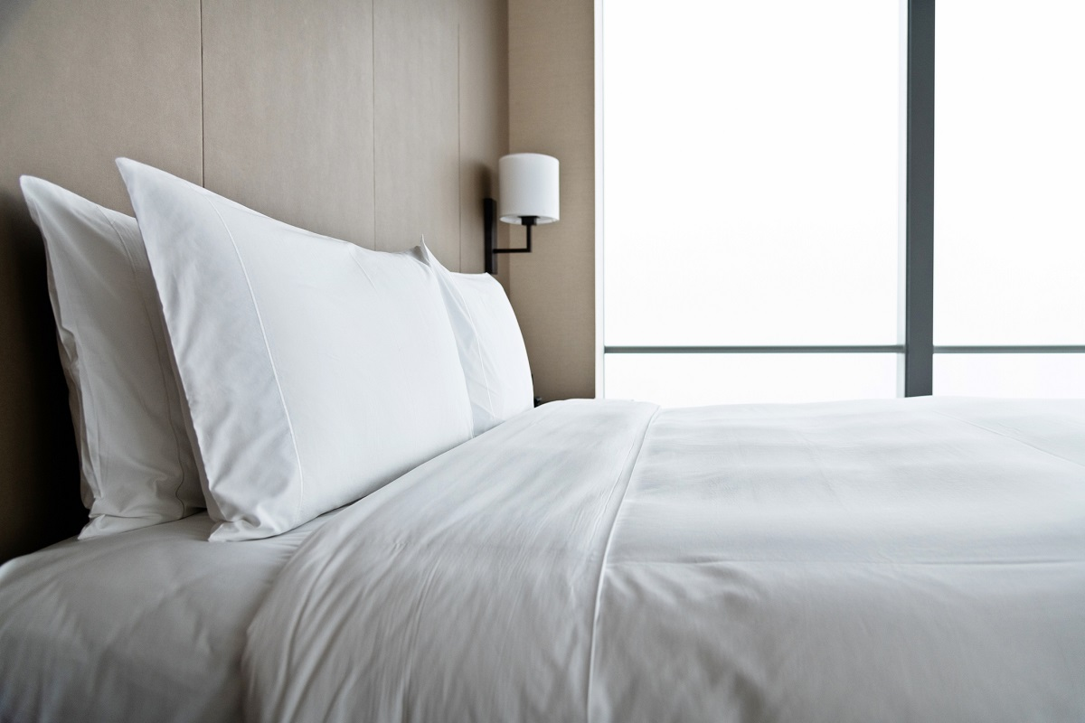 clean hotel bed with two white pillows and white sheets