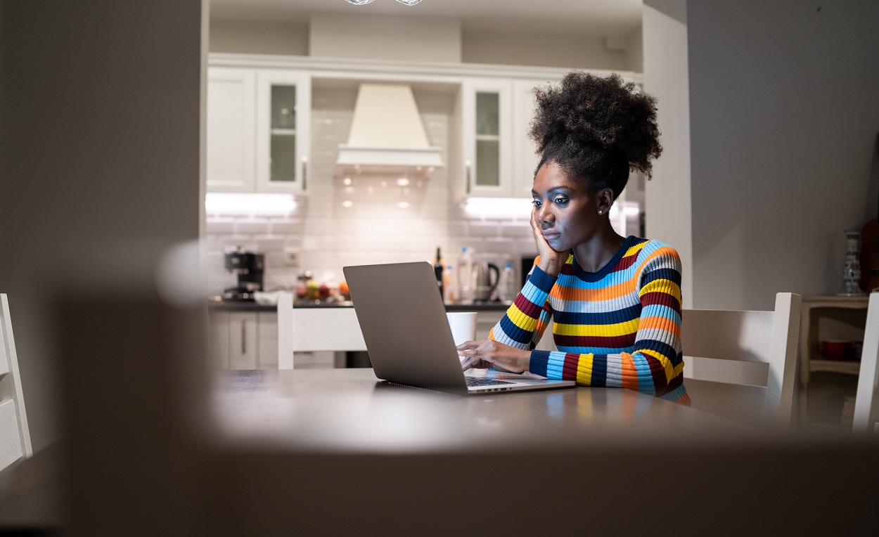 woman sitting at her dining room table at home looking at her laptop