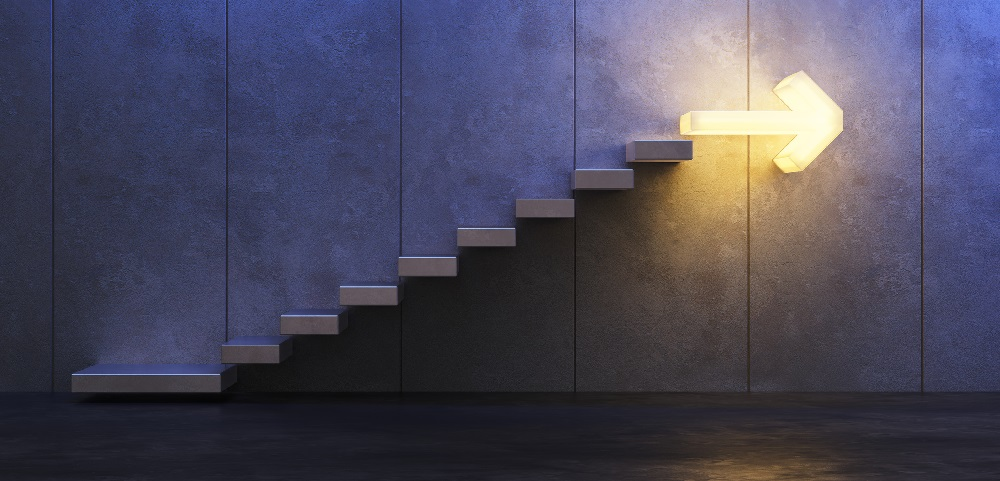 Steps along a wall, the top step is illuminated and shaped like an arrow pointing forward