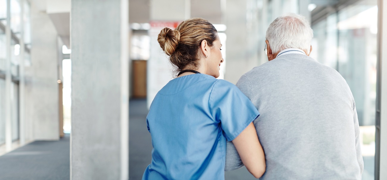 healthcare worker escorting elderly man down hospital hallway