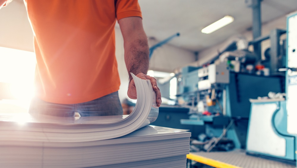 Man in orange polo shirt and blue jeans picking up a stack of paper, large commercial printing is in the background