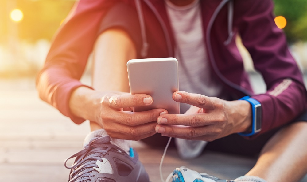 Person dressed for exercise, sitting on the ground checking fitness app on smartphone
