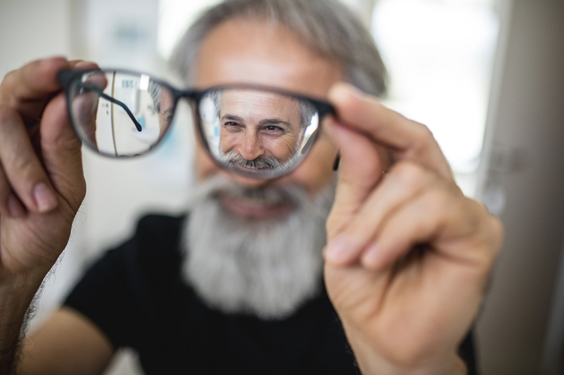Older man with gray beard holding his eyeglasses out away from his face